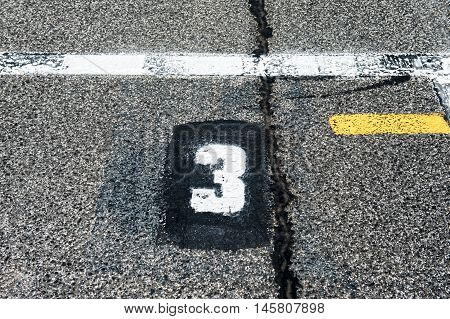 Number three position sign on speedway starting track with yellow line and damaged old asphalt