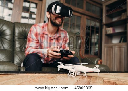 Man try to control drone in vr glasses. White unmanned aerial vehicle with camera on table before flight, guy in virtual reality headset with remote controller on background