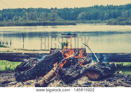 Rustic bonfire by the lake in the forest on the background of blurry boat with fisherman on the lake vintage photo.