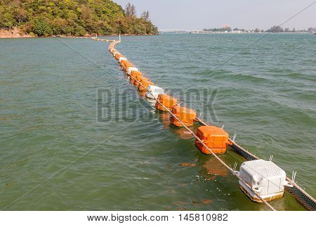 Line of floating orange and white buoys for marking safety zone.
