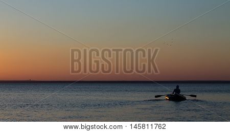 Man with oars on an inflatable boat on the water in the sea