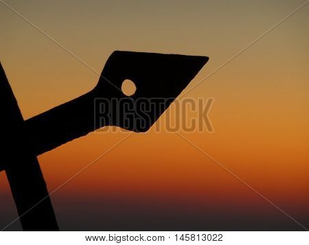 Silhouette of Arrow Shaped Wrought Iron Against the Orange Gradation of Sunset sky, Santorini island of Greece, background