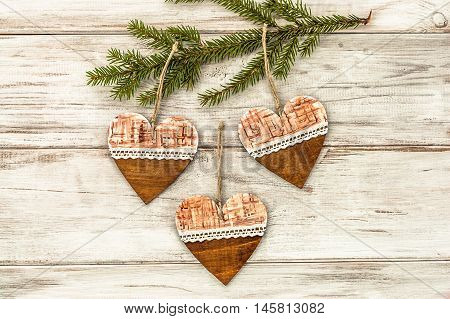 Green Christmas tree branch with hanging decoration on wooden background