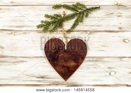 Hanging decoration on christmas tree branch on wooden background