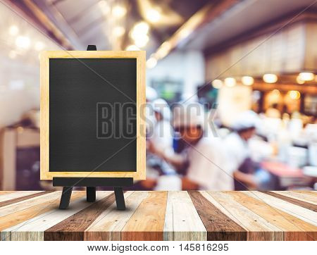 Blackboard Menu With Easel On Wooden Table With Blur Open Kitchen At  Restaurant Background, Copy Sp