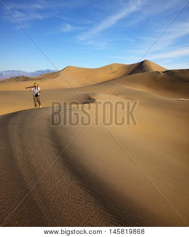 Woman - photographer with camera and tripod is on the curved ridge of dunes. Bright sunny morning in a picturesque part of Death Valley. Mesquite Flat Sand Dunes