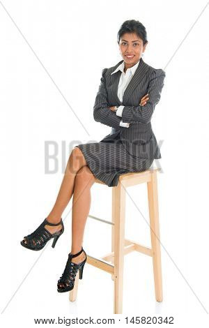 Full length black businesswoman sitting on high chair and arms crossed, isolated on white background.