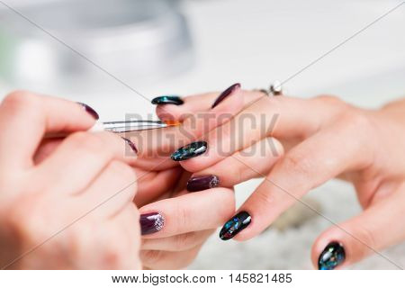 Painting fingernails in nail salon, toned image