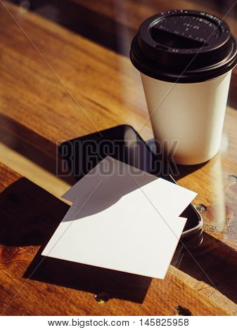 Closeup Empty White Business Card.Mockup.Mobile Phone High Textured Wood Table Take Away Coffee Cup.Work Modern Office Blurred Background.Blank Object Private Corporate Information Vertical Mock Up