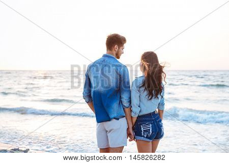 Back view of happy young couple standing and holding hands on the beach