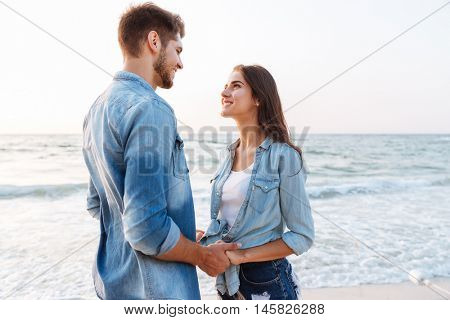 Happy young couple in love standing and holding hands on the beach