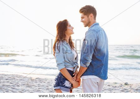 Happy young couple standing and holding hands on the beach