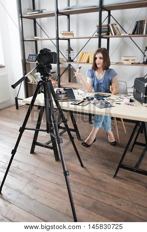 Young pretty blogger recording video on camera. Modern occupation, woman telling about makeup cosmetics in her vlog