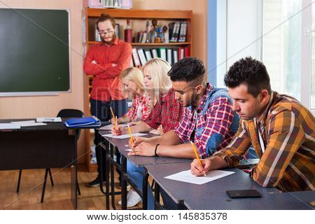 Student Group Write Test, Professor Observing, Young Diverse People Sit Desk University Classroom Examination High Shool Education