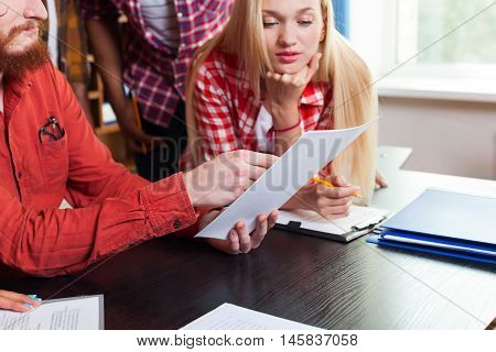 Close Up Student High School Group Looking At Paper Document With Professor Sitting At Desk, Young People Teacher Discuss Communicate University Classroom