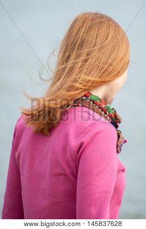 Portrait from back of a red-haired woman