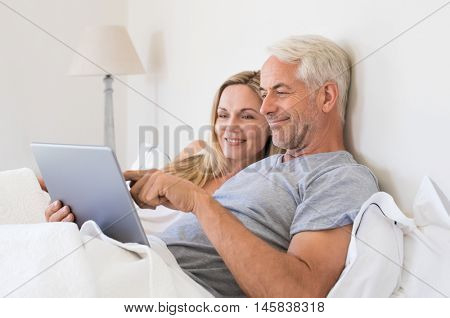Senior couple using digital tablet while lying in bed at home. Happy senior couple surfing on the tablet in bedroom. Retired man and smiling woman planning on laptop their summer vacation.