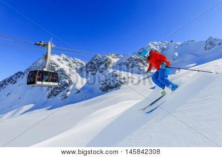 Skier skiing downhill in high mountains in fresh powder snow. Snow mountain range and cable railway in background. Mt Fort Peak Alps region Switzerland.