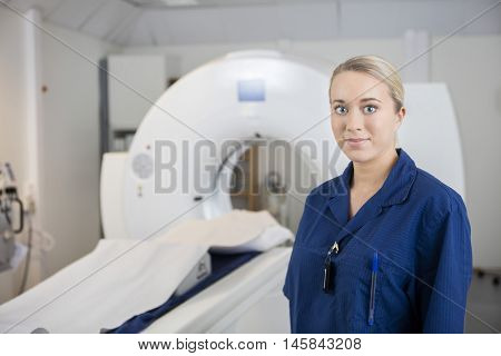 Young Professional Standing By MRI Machine In Clinic