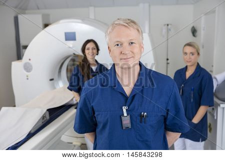 Confident Male Radiologist With Colleagues Standing By MRI Machi