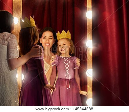Cute little actress. Young mother and her daughter child girl in Princess costume on the background of theatrical scenes and mirrors.