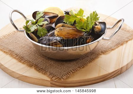 cooked scottish mussels with parsley and lemon in a metal bowl on jute