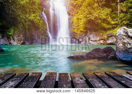 Waterfall in deep forest and wood pier for background. Can be used for display or montage your products.