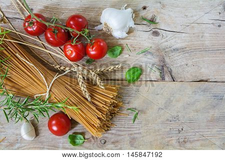 Ingredients for an Italian pasta meal with wholemeal spaghetti wheat ears tomatoes garlic and basil herbs as seen from above on a rustic wooden background generous copy space
