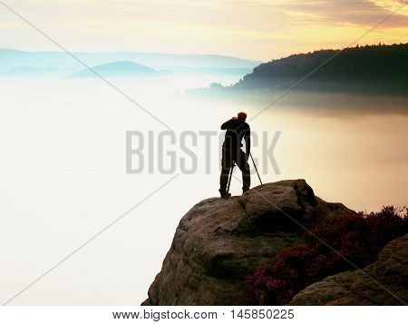 Professional Use Mirror Camera And Tripod On Peak Of Rock