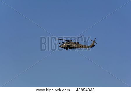 Military helicopter UH-60 Black Hawk against the blue sky