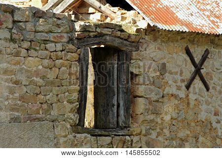 Old stone building ruin with wooden window