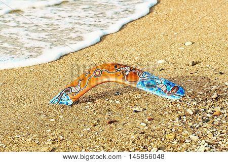 Colorful boomerang on sandy beach near sea surf.Toned image.