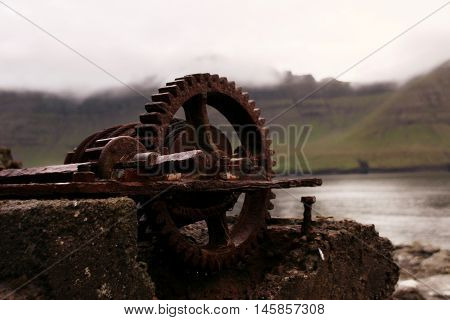 Rusted iron wheal at the coastline in the Faroe Islands