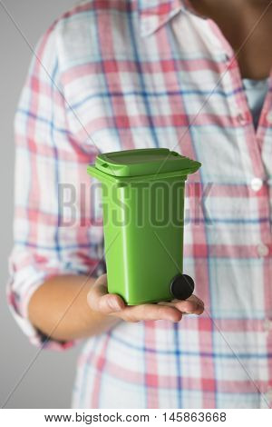 Close Up Of Woman Holding Model Recycling Bin