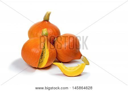 Three pumpkins are lying on a white background. One pumpkin is sliced. A piece of pumpkin is lying in front of others.