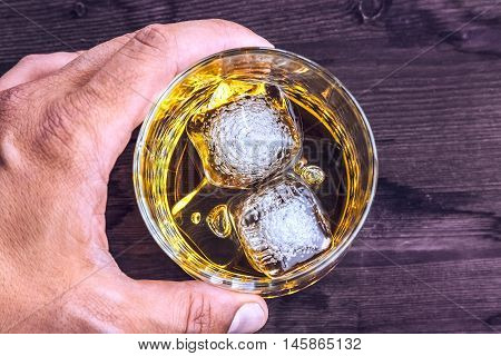 Top Of View Of Man Holding Glass Of Whiskey With Ice Cubes On Wood Table Background, Focus On Ice Cu
