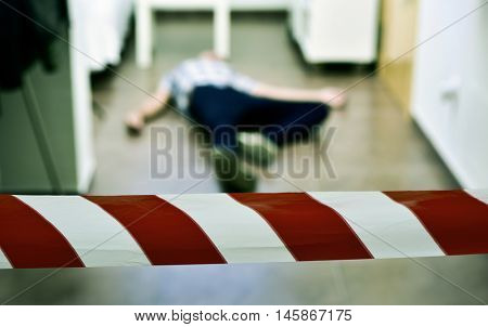 detail of a crime scene with the dead body of a young man lying in the floor indoors, with a red and white police tape in the foreground