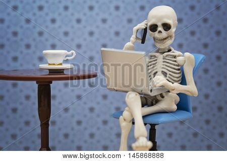 Skeleton talking with smartphone while working with laptop