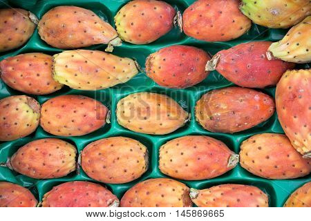 Prickly pear cactus fruits called also Opuntia ficus-indica Indian fig opuntia barbary fig tuna in a box for sale on the greek market. Fruits of prickly pear cactus on a market. Horizontal. Close.