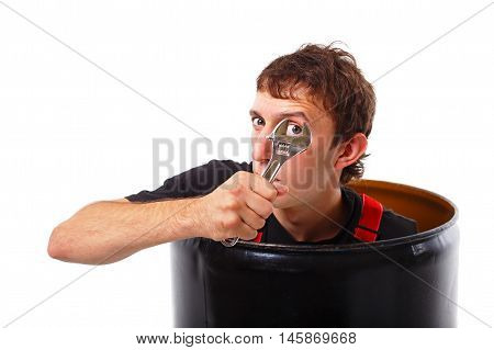 worker with wrench comes out of the pipe. young man holding adjustable wrench and plans to work with the instrument. looking at camera. isolated on a white background