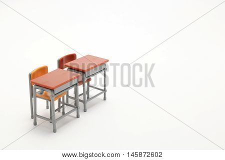 Two miniature school desks on white background. Classroom image.