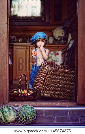 Little boy standing on the doorstep in a denim hat and shorts