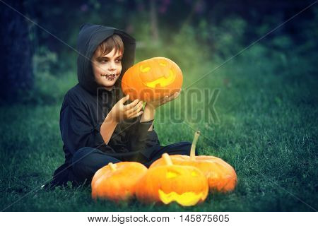 Child in scary costume holding pumpkin ln. Child in halloween outfit at night