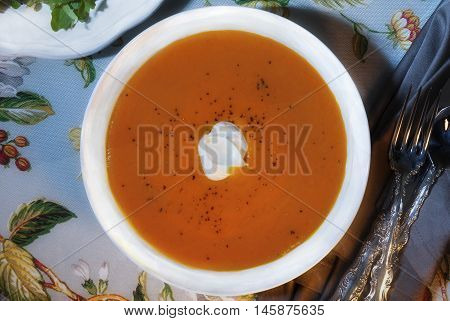 Low key image of carrot ginger tofu puree soup on a floral table cloth with dappled sunlight on the soup.