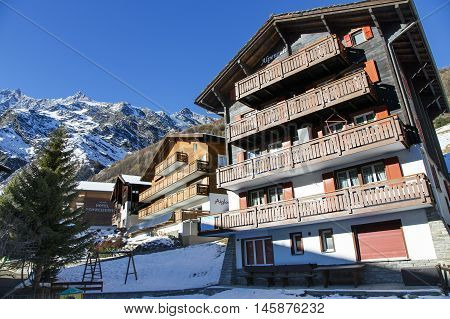 SWITZERLAND, SAAS-FEE, DECEMBER, 26, 2015 - Modern wooden hotels on a background mountains in the charming Swiss resort of Saas-Fee, Switzerland