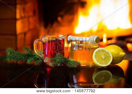 Christmas New Year composition. Glass of mulled red wine or hot drink tea, jar of honey and lemon with christmas decoration - fir branches in front of warm fireplace. Relaxed atmosphere near fireplace