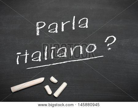 Learning Italian language concept of teacher or student writing parla italiano (do you speak Italian) on blackboard / chalkboard.