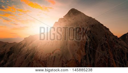 mountain view with snow silhouette at sunset scene with sun fall and ray light clouds in background warm colorful sky