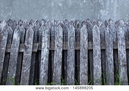 old wooden fence dismantled. ruined fence on the background of the new concrete fence. ruined wooden fence left near a gray wall. empty space for your text
