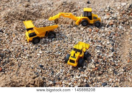 toy excavator, truck and loader in a quarry. the concept of stone mining. toy construction car on the beach